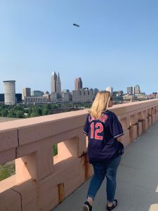 a person in a Cleveland Indians jersey crosses a bridge in front of the city skyline