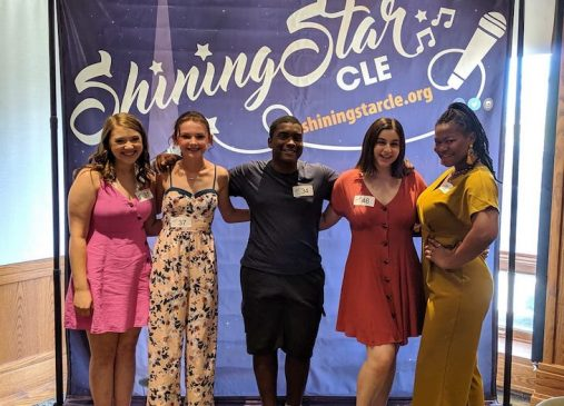 a group of people stand in front of a step and repeat banner