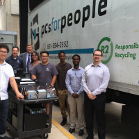 A group of people stand in front of PCs for People truck