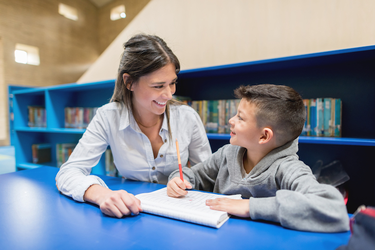 a woman helps a boy with homework at a library desk