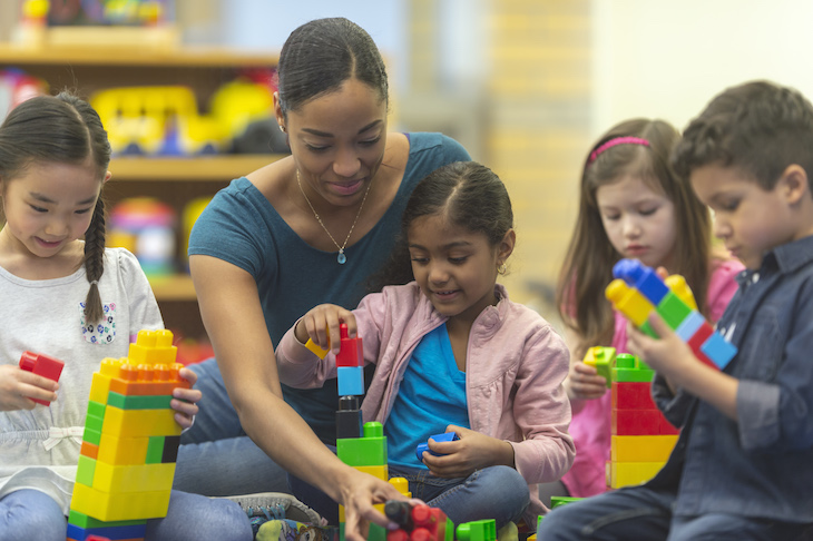 A teacher and her kindergarten students are playing with toy building blocks in their classroom.