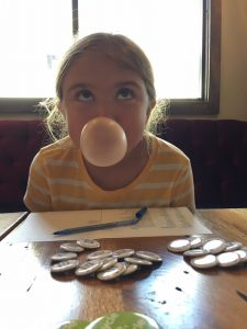 a girl blows a bubble with gum