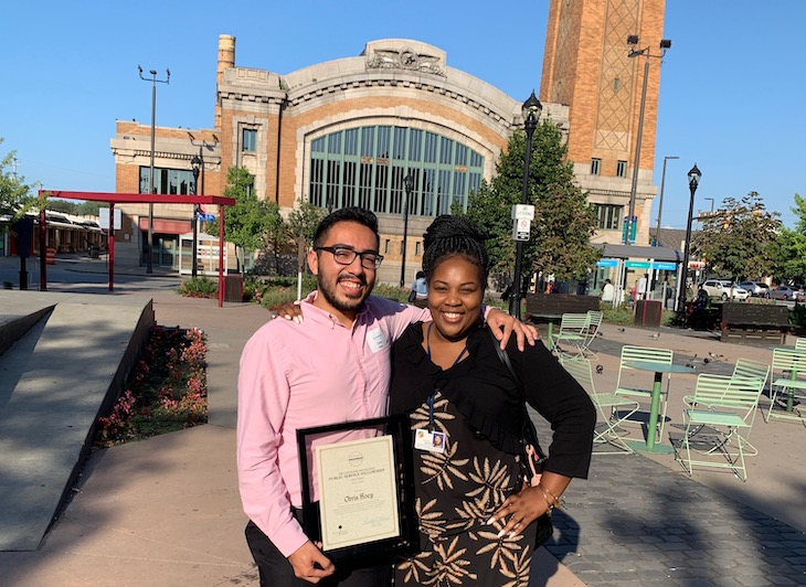 Christopher and a woman stand outside a building in Cleveland