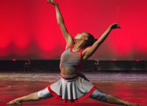 A girl performs the splits while dancing onstage