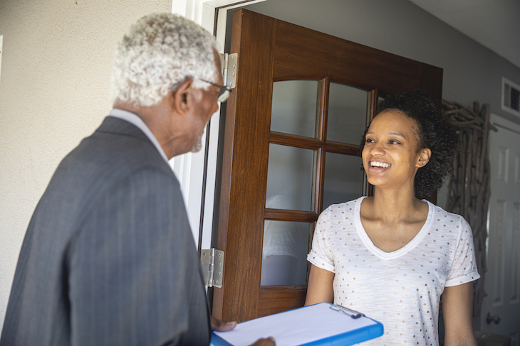 A man speaks to a woman at her front door
