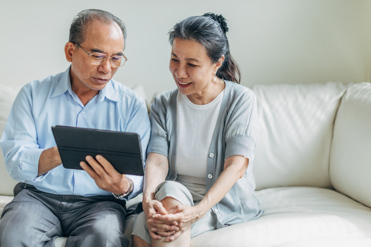 Man and woman, senior married couple using digital tablet at home together.
