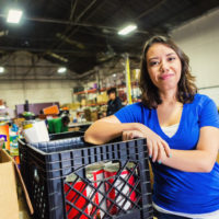 A woman stands inside a food bank warehouse