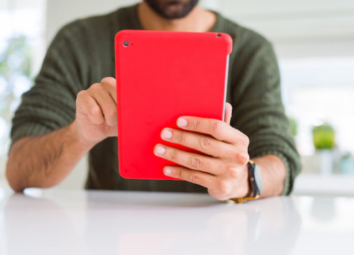 man seated at table holds red ipad