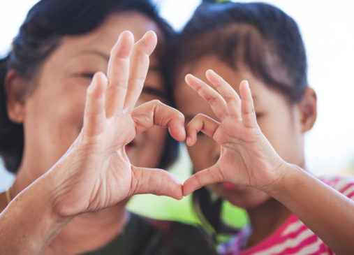 mother and little girl making heart shape with hands together with love