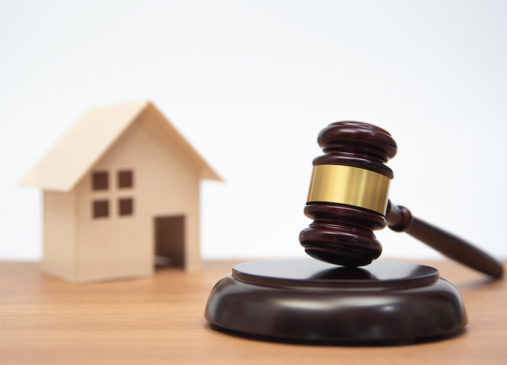 Miniature House on wooden table and judge gavel.