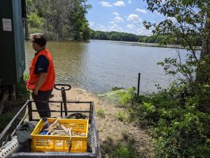 Photo of a man and cart of equipment standing next to a lake