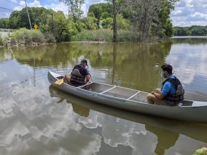 Two men paddle a canoe