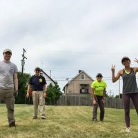 Four people stand in a field in the city