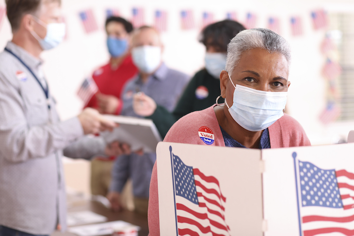woman casts her vote in a mask