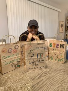 A woman poses with STEM kits