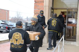 Members of Alpha Phi Alpha pack supplies for delivery