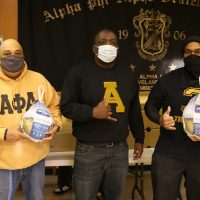 Photo of three members of the Cleveland chapter of Alpha Phi Alpha at a food distribution event