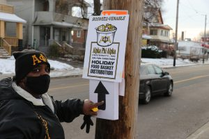 Member of Alpha Phi Alpha fraternity pointing to a holiday food distribution event sign
