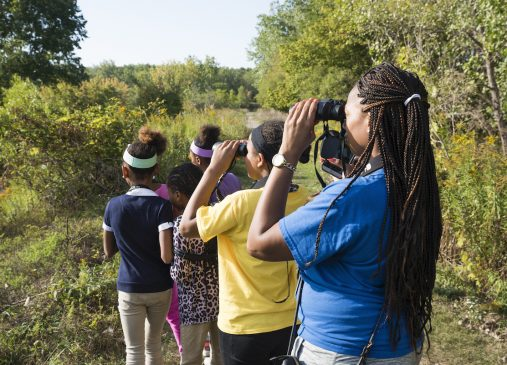 Young people outdoors using binoculars