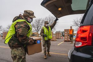 Volunteers load food at drive-through distribution event