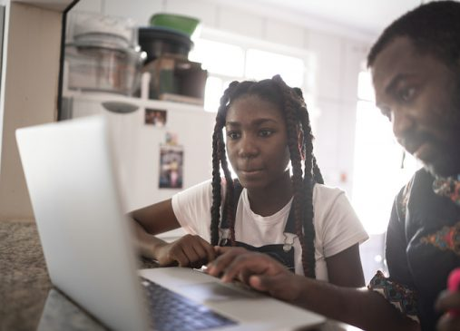 Dad helping his teenager doing homework at home on computer