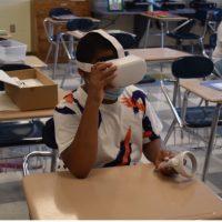 Boy sits at desk wearing virtual reality head set