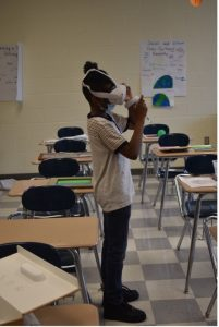Boy stands in classroom wearing virtual reality head set