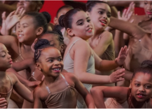 A group of young dancers perform onstage