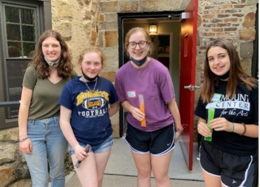 Four girls stand in front of a building