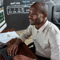 Black man sits at trading desk