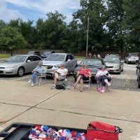 A group of women sit in folding chairs outside in a parking lot.