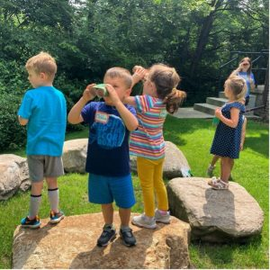 A group of young children explore outdoors