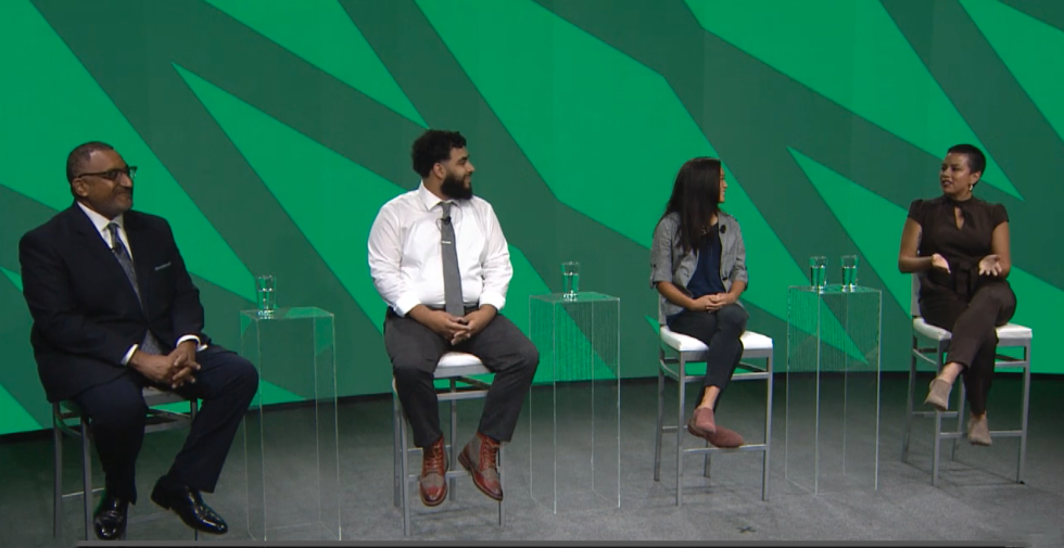 Four people sit in chairs against a green backdrop.