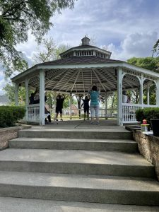 A group of people do Tai-Chi under a gazebo.