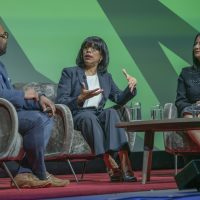 Three panelists sit onstage in chairs