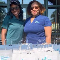 Two women stand behind of a table of gift bags